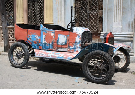 A colourful tattered open top vintage car in a street of Havana, Cuba.