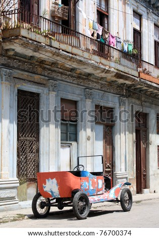 A colourful tattered open top 1912 vintage car in a street of Havana, Cuba. - stock photo