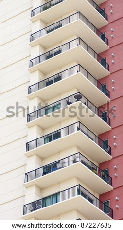 A column of condo balconies by a red stucco wall - stock photo
