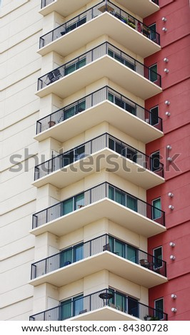 A column of condominium balconies next to a red stucco wall - stock photo