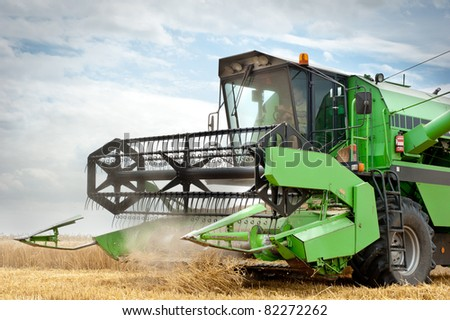 A combine harvester working in a wheat field - stock photo