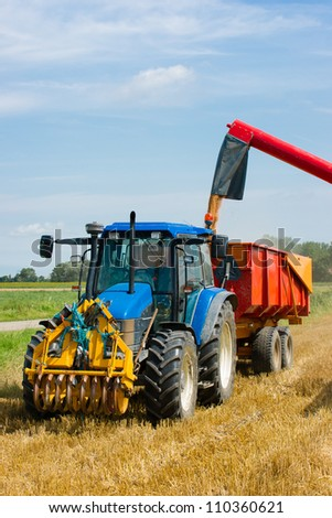 A combine/tractor is harvesting the wheat on a sunny day - stock photo