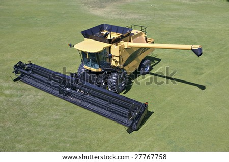 A combine tractor parked on green grass - stock photo
