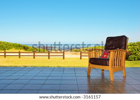 A comfortable leather chair on a patio at a seaside residence or holiday home