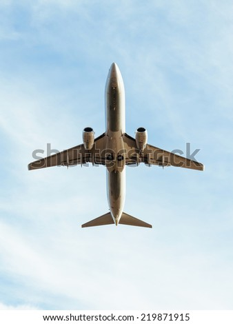 A Commercial air plane take off, seen from below. - stock photo