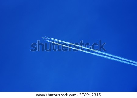 A commercial airplane flying at high altitude leaving contrails or condensation trails against a dark blue sky.