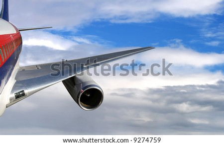 A commercial airplane flying through the clouds - stock photo