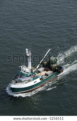 A commercial fishing boat heading out into the northern Pacific. - stock photo