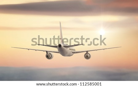 A commercial Jet flying high above the clouds into the sunset. - stock photo
