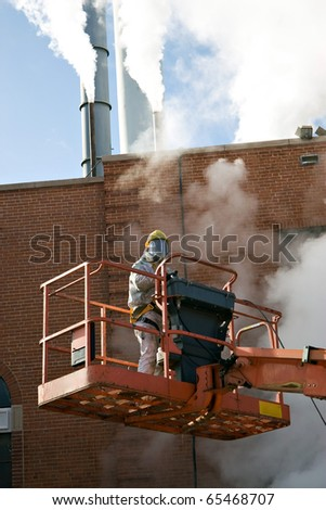 A commercial painter suited up and standing on a hydraulic lift he is using. - stock photo