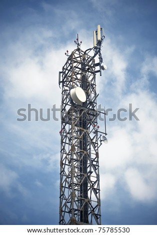 A communications tower against background of stormy clouds in the blue sky. - stock photo