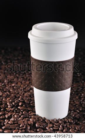 A commuter coffee cup rests on roasted coffee beans. 24MP camera. - stock photo