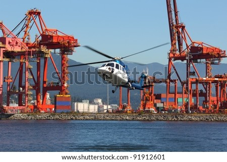 A commuter helicopter arrives at downtown Vancouver's helipad on Burrard Inlet in front of the container port and cargo cranes. The Coast Mountains rise in the background. British Columbia, Canada.