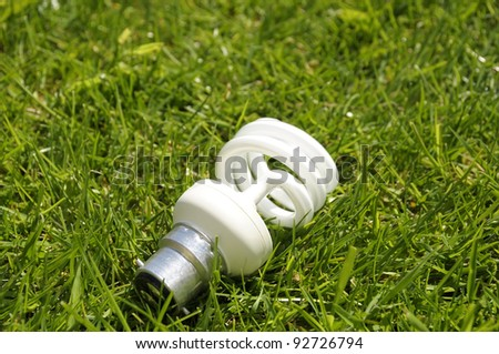A compact fluorescent lightbulb on grass. - stock photo