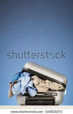 A compact suitcase with too many things to wear. A concept about packing too much for a trip. - stock photo