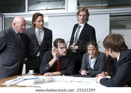 A company director discussing plans with his young staff members