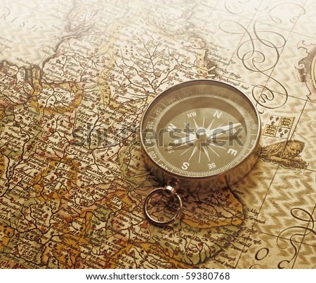 A compass lies on an age-old map - stock photo