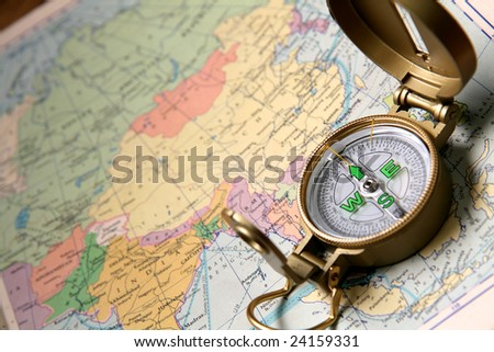 A compass on the world map of the atlas. - stock photo