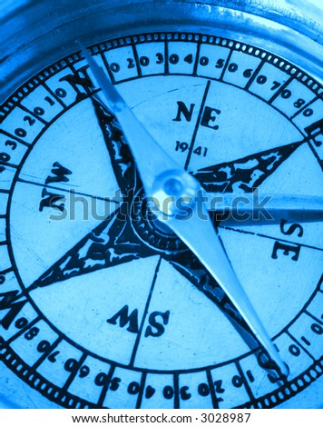 A compass pointing North, extreme close-up, monchrome with a blue tint.