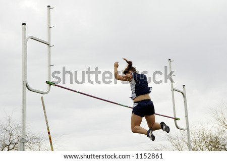 A competitor clears the bar in the women's pole vault event during a college track meet.
