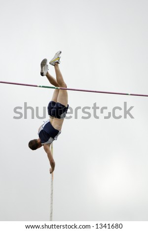 A competitor in the men's pole vault event during a college track meet.