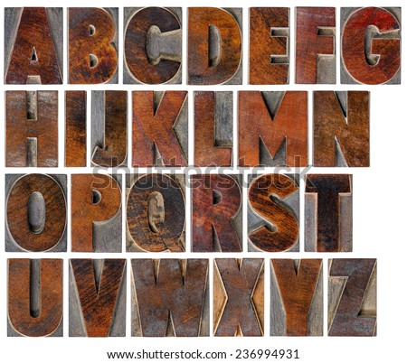 a complete English uppercase alphabet - a collage of 26 isolated antique wood letterpress printing blocks with ink patina - stock photo
