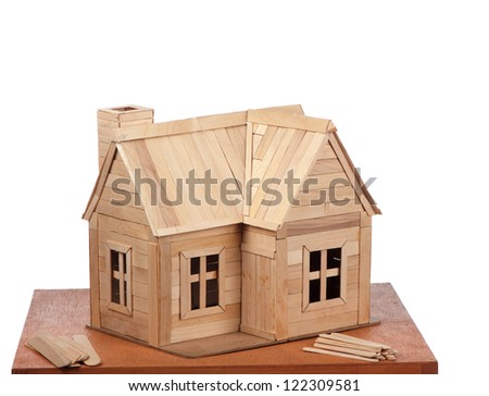 A completed popsicle stick house is displayed with some unused building material. - stock photo