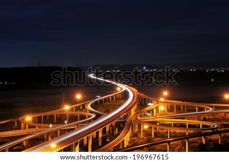 A complex highway junction shown during the night. - stock photo