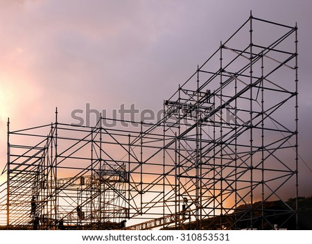 A complex scaffold setup for a stage for an outdoor concert seen at sunset - stock photo