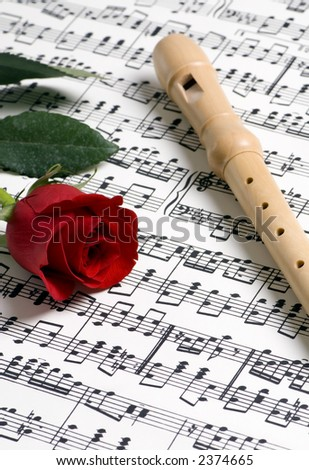 A complicated musical piece with a single rose and a flute on top. Representing the love of music, the simplicity of music and also the complexity.