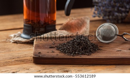 A composition of a tea ball and dry black tea leaves on wooden board.