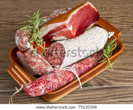 A composition of different sorts of cold cuts on wooden table - stock photo