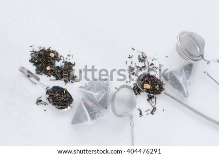 A composition of tea bags, tea balls and green tea leaves with pomegranate and raspberries. Everything is arranged on a marble cutting board.