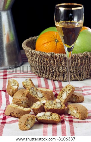 "A composition with the typical tuscan buscuits called ""cantucci"" with a glass filled with ""vin santo"" (holy wine), a tuscan dessert wine"