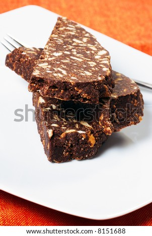 A composition with three slices of chocolate salami, a typical italian cake made with chocolate, butter and crumbled biscuits