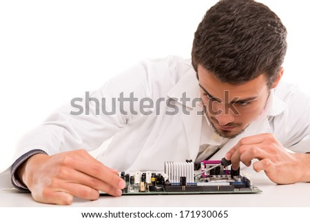 A computer engineer or technician, working on a computer motherboard - stock photo