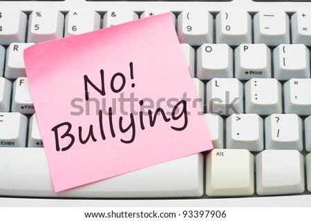 A computer keyboard with a sticky note saying no bulling, Stop internet bullying - stock photo