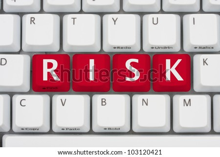 A computer keyboard with red keys spelling risk, Risk of computer viruses, spyware and identity the theft