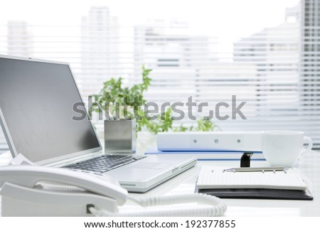 A computer laptop with a phone and calculator. - stock photo