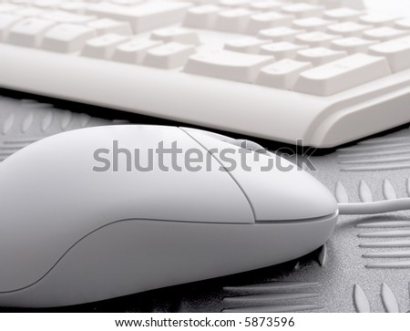 a computer mouse with a keyboard on the background