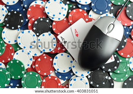 A computer mouse with poker chipsand 2 ace cards symbolizing on line poker - stock photo