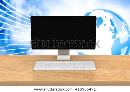 A computer over a desk against global business graphic in blue