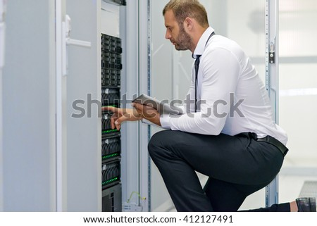 A computer technician connecting cables  - stock photo