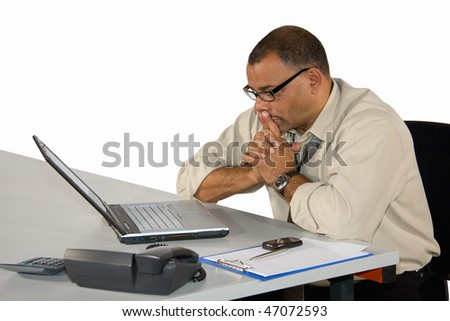 a concentrated working mature African-American businessman in front of his laptop, isolated on white background - stock photo