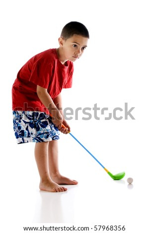 A concentrating, barefoot kindergartner preparing to hit a golf ball with his plastic club.  Isolated on white. - stock photo
