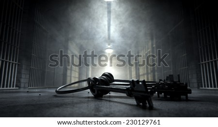 A concept image of an eerie corridor in a prison at night showing jail cells dimly illuminated by various ominous lights and a bunch of cell keys laying ominously on the floor - stock photo
