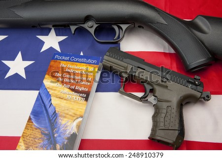 A concept image of liberty showing a pistol and rifle with the constitution booklet on the American flag, - stock photo
