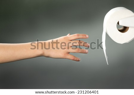 A concept image of reaching for the toilet paper. - stock photo