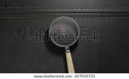 A concept image showing a regular stitched sheet of black leather with an embossed stamp reading genuine but magnified by a magnifying glass the one letter reads the word fake - stock photo