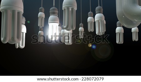 A concept image showing unlit dangling fluorescent light bulbs with one shining brighly showing leadership and innovation on an isolated dark background - stock photo